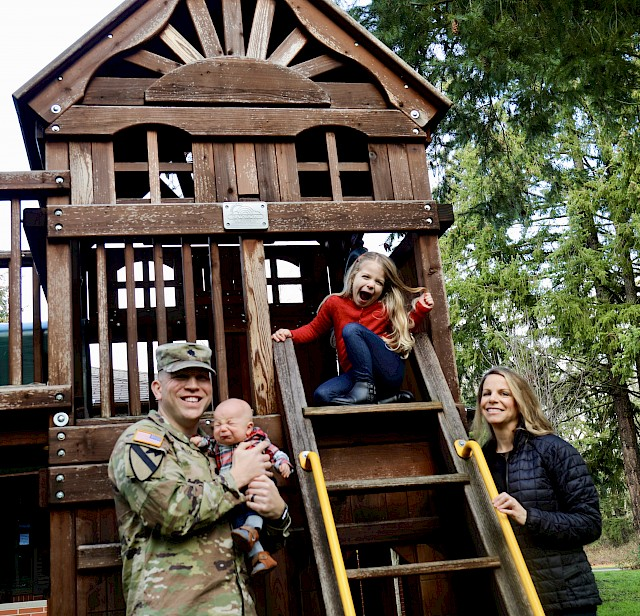 Army Lt. Col. John Miller and his family pose outside the Joint Base Lewis-McChord Army Fisher House in Washington.